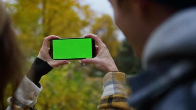Closeup Smartphone with Green Screen in Girls Hands