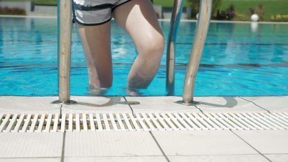 Thumbnail for Woman Going Down Stairs In Water Swimming Pool