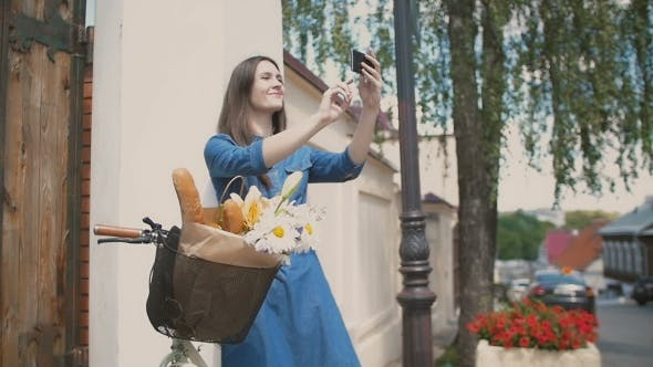 Thumbnail for Brunette Girl Touching Her Hair, Taking Selfie, Standing With a Bike With Flowers And Bread In a