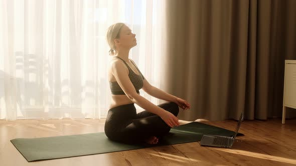 Woman doing yoga and meditating online to group of people on laptop.