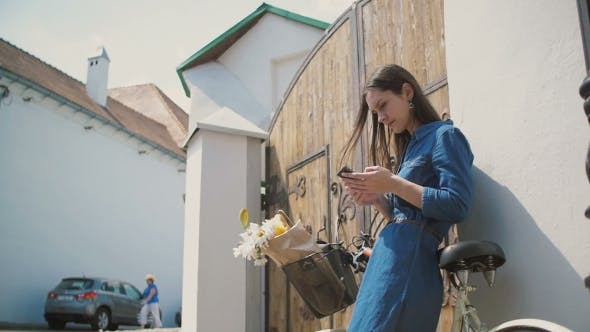 Thumbnail for Happy Brunette Girl Laughing And Talking On The Phone With a Bike And Flowers In a Basket, Using Her