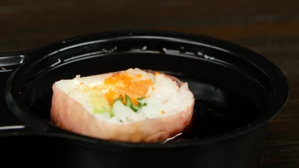 Thumbnail for Person Lowers His Sushi In Soy Sauce By Chopsticks.
