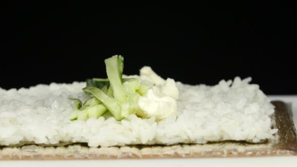 Thumbnail for Sushi Chef Puts The Filling In The Rolls.