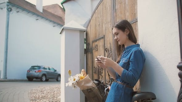 Cover Image for Brunette Girl Using Her Smartphone Standing Near Building With a Bike With Flowers In a Basket,