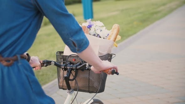 Thumbnail for Girl Hands On a Handlebar Of a Bicycle, Flowers And Bread In a Basket, Cycling In The City