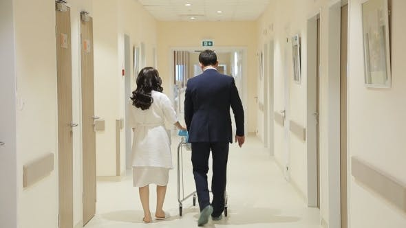 Thumbnail for Young Family Walks Down The Hallway Of The Hospital