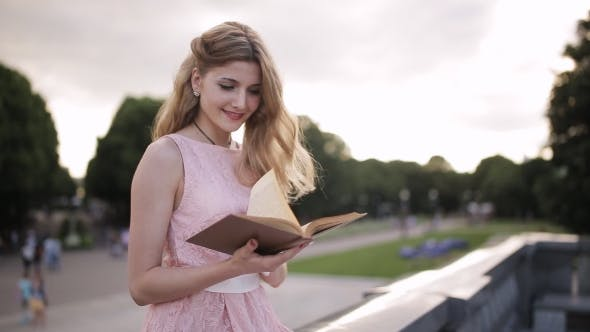 Thumbnail for Young Attractive Girl Reading a Book With An Interest In a Summer Park