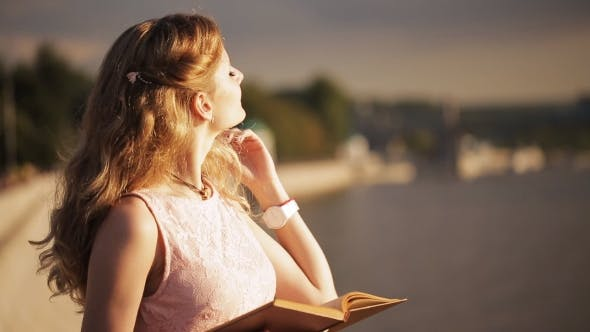 Cover Image for Cute Little Girl With Book In Hand Straightens The Hair At Sunset Promenade