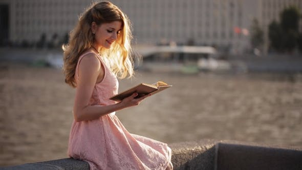 Thumbnail for Happy Girl Reading a Book On The Waterfront At Sunset