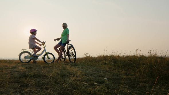Thumbnail for Mom And Child Meet The Sunset On Bicycles Admiring The Sunset