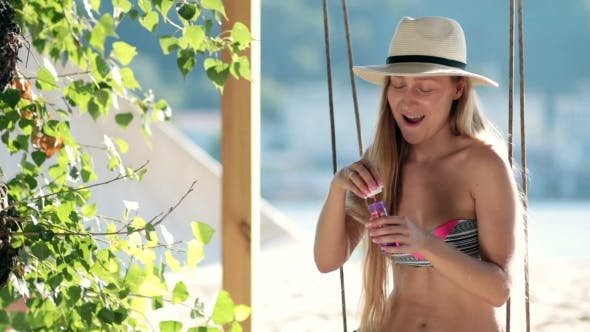 Thumbnail for Stunning Blonde Woman Sitting On a Swing On Beach