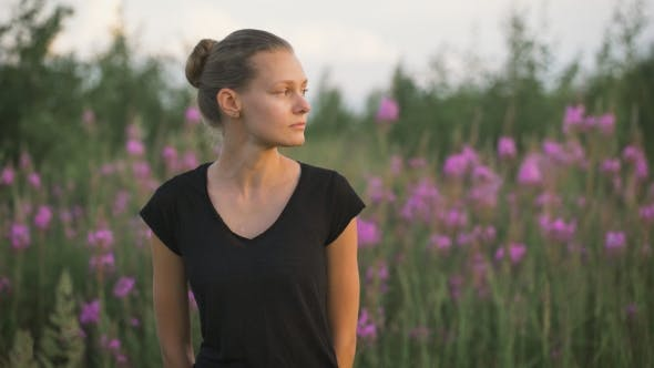 Thumbnail for Beautiful Young Healthy Woman Standing At a Green Field And Looking Away
