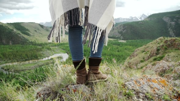 Thumbnail for Young Beautiful Woman Traveler Wearing Hat And Poncho Relaxing On The Top Of The Hill With Mountains