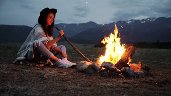 Thumbnail for The Girl In a Warm Sweater Sitting By The Fire In The Evening.
