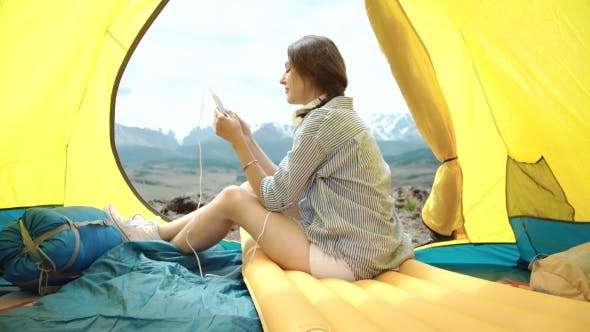 Thumbnail for A Woman On Her Phone While In Her Tent And Sleeping Bag