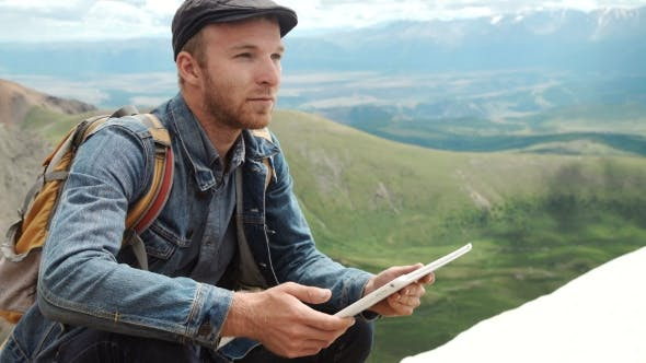 Thumbnail for Man's Hands Touching Screen Of Digital Tablet On The Background Of Mountains
