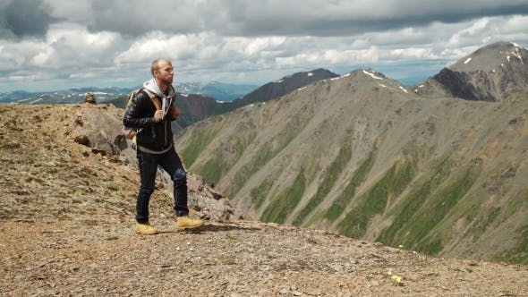 Thumbnail for Hiker With Backpack Standing On Top Of a Mountain