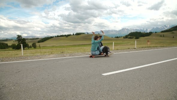 Thumbnail for Best Friends Having Fun With Skateboard On Open Road. Young Man And Woman Longboarding Together