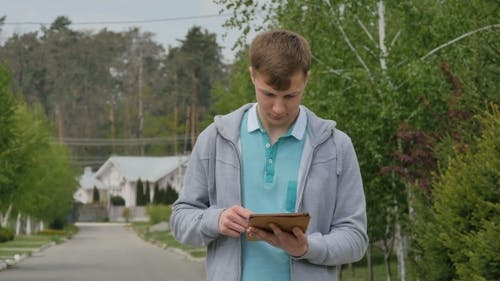 A Young Boy Stares At The Tablet.
