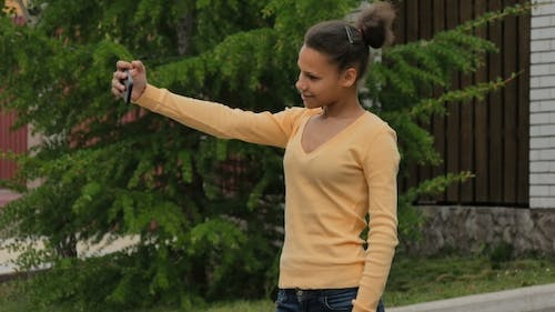 Young Biracial Girl Makes Selfie Phone Standing On The Street