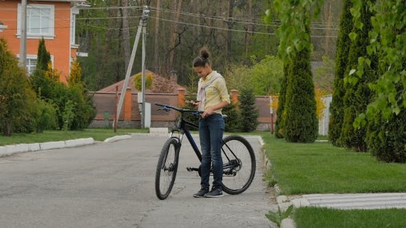 Thumbnail for Girl Typing On The Phone And Holding a Bicycle