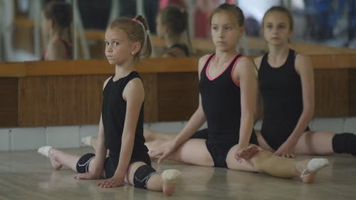 Young Girls Warm Up In The Gym. The Exercises In Rhythmic Gymnastics.