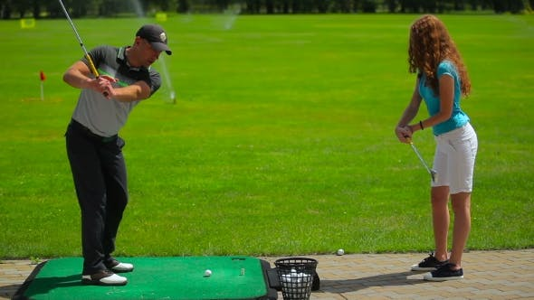 Thumbnail for Man Shows Girl How To Hit The Ball In Golf