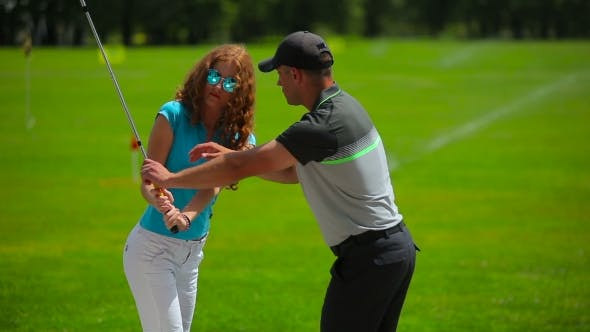 Thumbnail for Young Man Train Woman How To Hit Ball In Golf