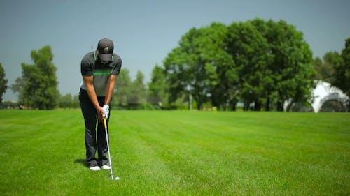 Junge männliche spielen golf bei der golf feld
