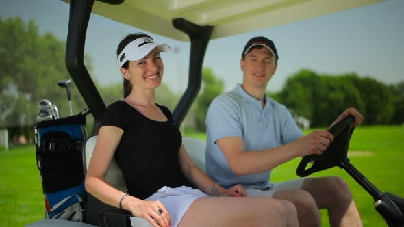 Thumbnail for Young Couple Smiling in Cart at the Course