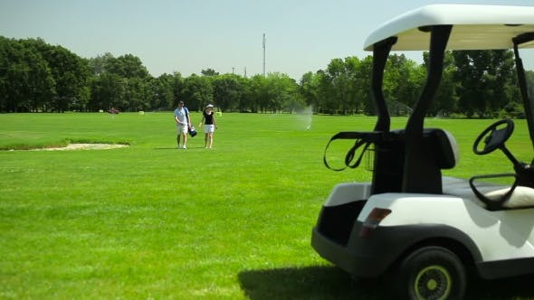 Thumbnail for The Couple Turn Back To The Cart At The Course