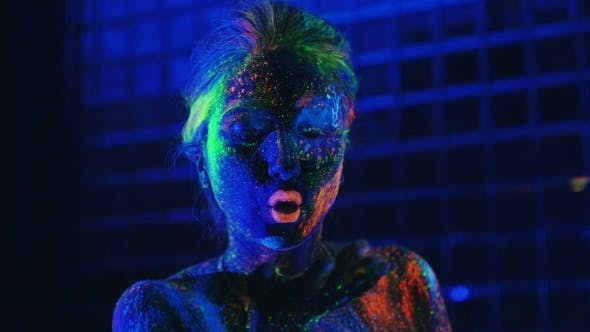 Thumbnail for Girl In Ultraviolet Light Blows Pink Fluorescent Powder With Palm