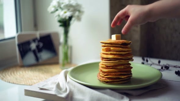 Thumbnail for Hand Puts Piece Of Butter On Stack Of Pancakes