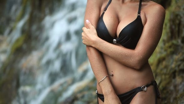 Thumbnail for Beautiful Young Girl In Bathing Suit Standing At The Foot Of The Waterfall