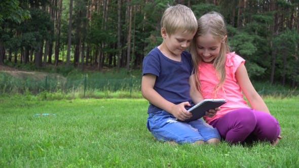 Thumbnail for Two Kids Playing With Tablet Outdoors