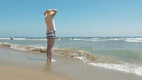 Frau steht am Strand mit einem Jute-Hut auf