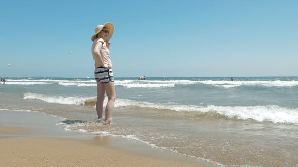 Thumbnail for Woman Is Standing At The Beach With a Jute Hat On