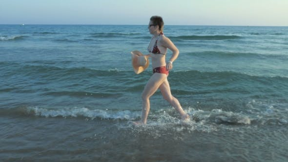 Thumbnail for A Female Running In Her Bathing Suit On The Beach