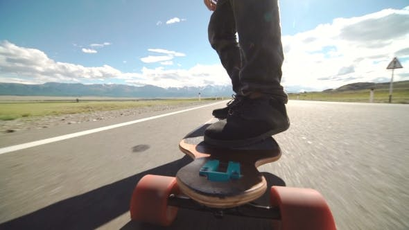 Guy On His Longboard Skate.  Of Longboard And Foot. Side View. Tracking Shot