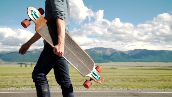 Thumbnail for Bearded Tattooed Man In a Red Shirt Posing With a Longboard.