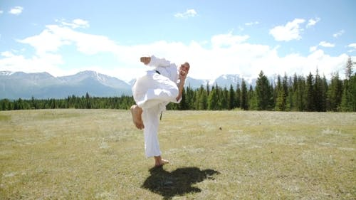 Fighter Performing Karate Stance Against Rock Crashing Down From Cliff
