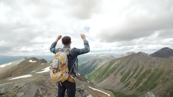 Thumbnail for Hiker With Backpack Standing On Top Of a Mountain With Raised Hands And Enjoying Sunrise