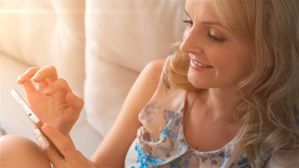 Thumbnail for Happy Smiling Girl Using SmartPhone Sitting on Sofa at Home 2