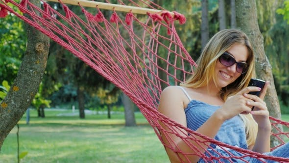 Thumbnail for Young Woman In Sunglasses Resting In a Hammock, Enjoy Telephone