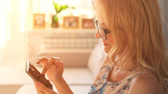 Thumbnail for Beautiful Girl Using Phone Sitting on Sofa Near Window 7