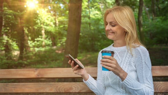 Thumbnail for Happy Smiling Girl Using a Smartphone in a City Park Sitting on a Bench 5