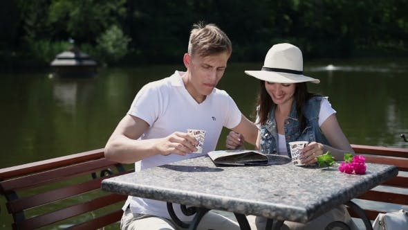 Thumbnail for Man And Girl Drinking Coffee Near The River