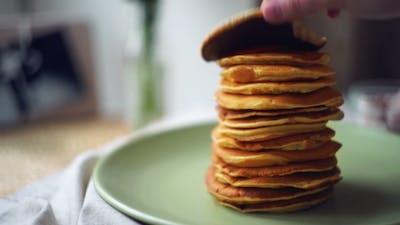 Man Take One Pancake From Stack Of Pancakes
