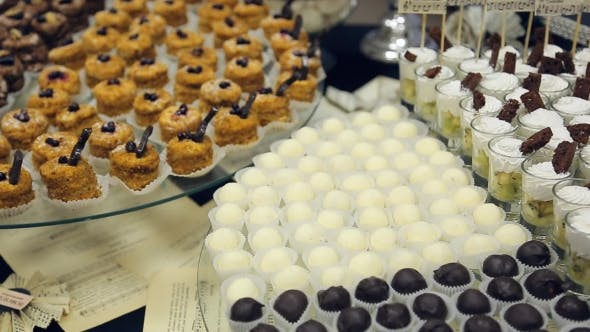 Thumbnail for Banquet Table And Laid Out a Variety Of Small Cakes, Candies, White And Dark Chocolate And a Glass