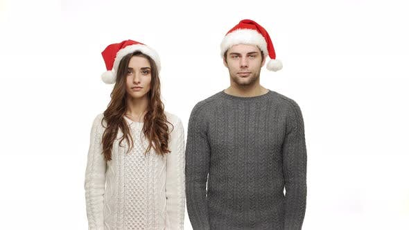Young Couple in Sweaters Showing Present and Show Shocking Expression To Camera.